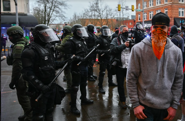 A right-wing protester stands before police during a Salem rally.