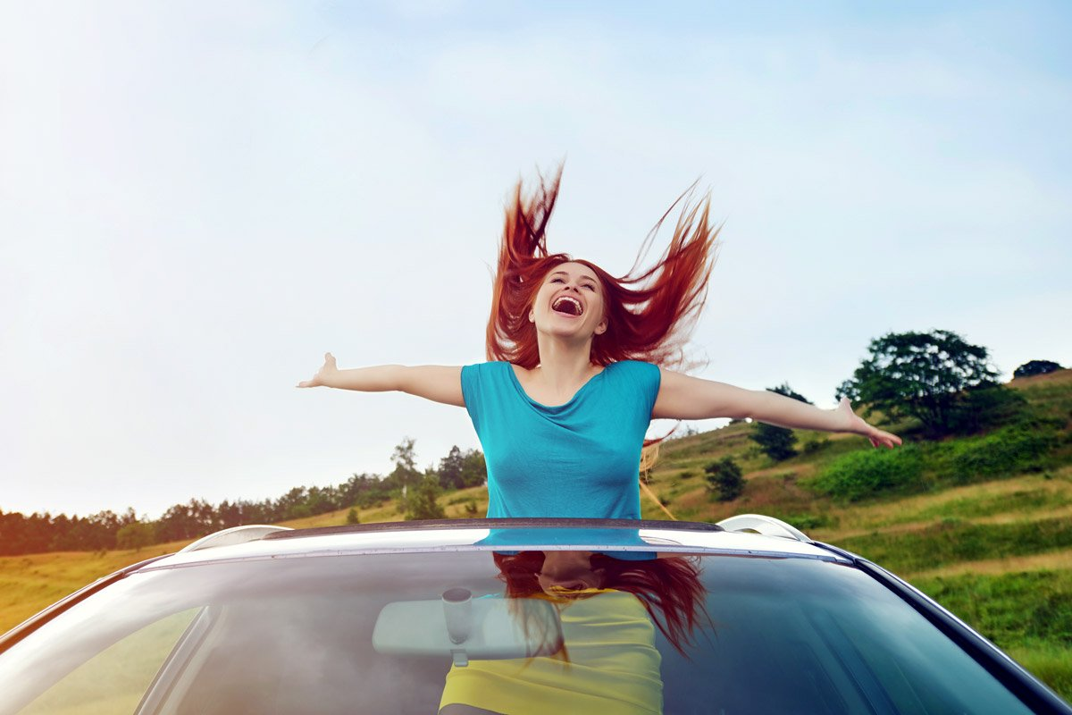 A woman stands from the sunroof of a car, catching the wind in her hair.