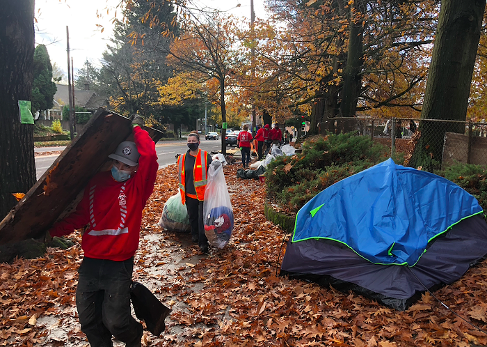 Portland city staff removes trash and belongings from a Laurelhust Park encampment.