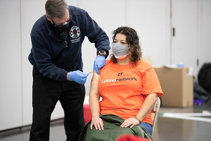 A person in an orange Latino Network shirt sits in a chair while a healthcare worker injects them with the vaccine.
