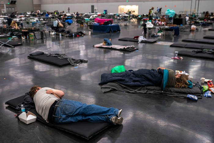 People lie down and sleep on mats spaced out in a large room.