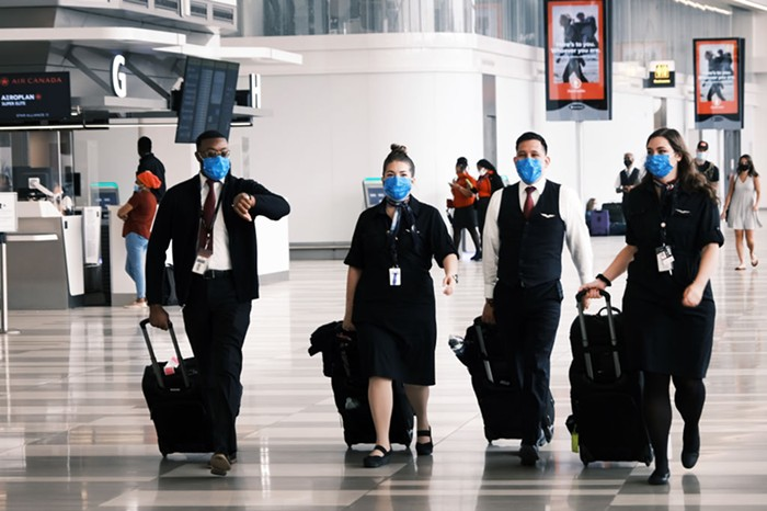 A pilot and three airplane staff walk through a terminal. All of them are wearing masks and the pilot is checking their watch.