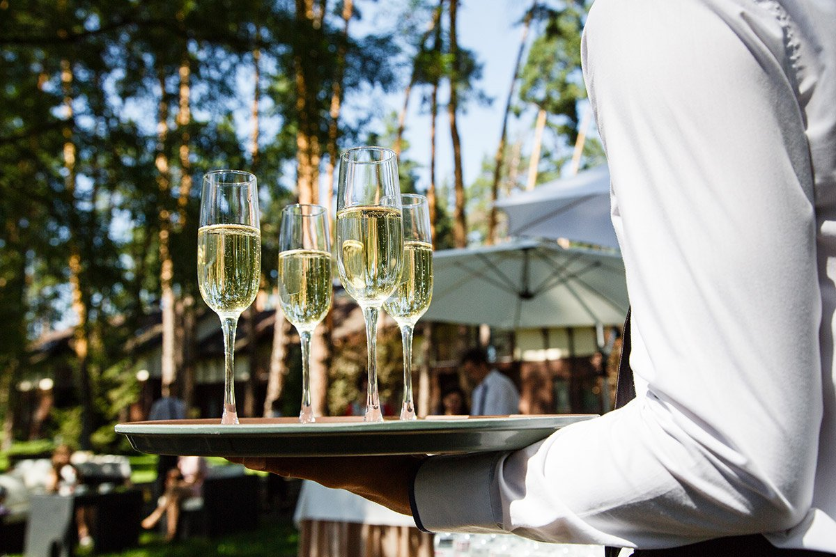 server holding champagne glasses at outdoor wedding