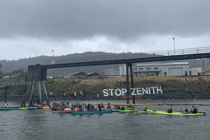 People in kayaks raise a sign reading stop zentih