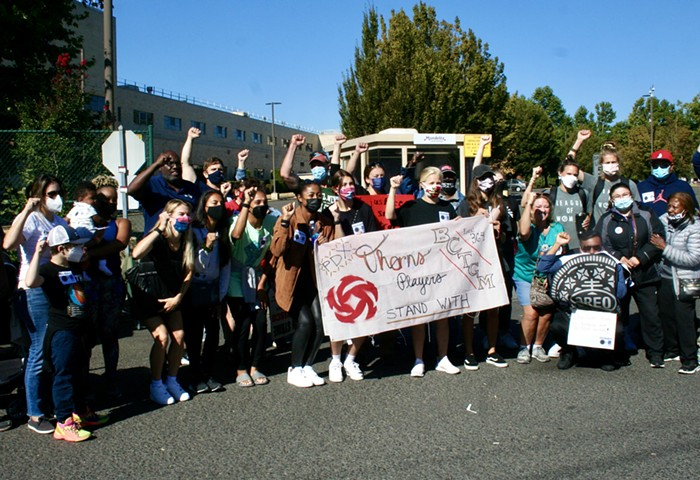 a group of people stand behind a banner reading pdx thorns players stand with bctgm