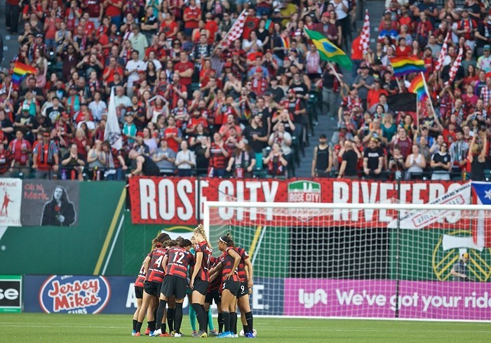 Portland Thorns on the field in 2019, backed by their supporters, the Rose City Riveters